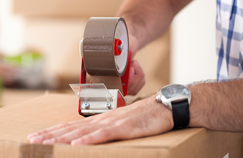 Close up of male hand packing cardboard box, concept moving hous